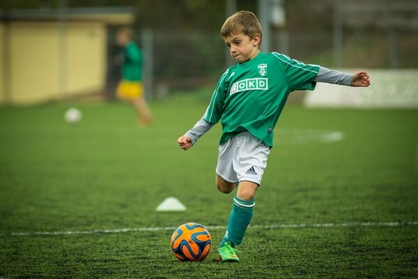 Kid playing football on the green pitch